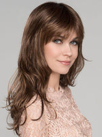 Pretty is a long, layered, and wavy wig with a full bang