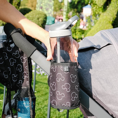 Disney Baby Cup 'N Stuff Stroller Cup Holder hanging on stroller with woman pulling bottle out of it
