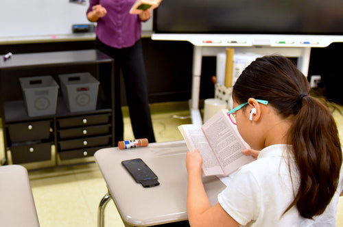 Middle-school girl student using Noopl with Airpods Pro on in classroom