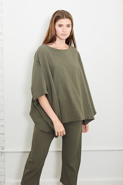 The cube top in moss by Uzi. It is an oversized top with a boat neckline, elbow length sleeves with dropped armholes and pre-washed. Model is 5'10 and wears one size.  Fits oversized One size  Length from shoulder 25″, chest at underarm 48″ Coarsely woven 100% cotton with slight wrinkle effect Sewn in Brooklyn, New York Parc Shop