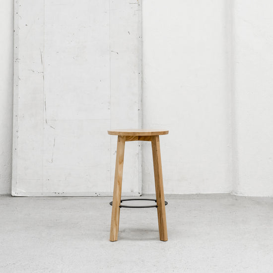 Round Scandinavian Oak barstool with metal footrest at EDITO Furniture