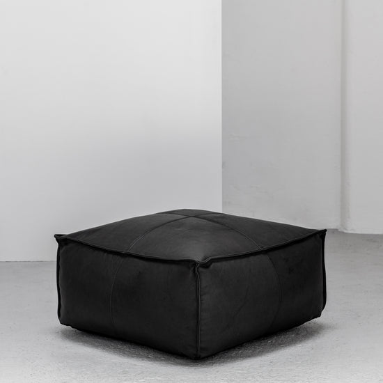 Large contemporary black leather ottoman with raw edge at EDITO Furniture
