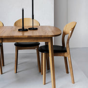 Oak dining table and oak dining chairs with black leather seat at EDITO Furniture