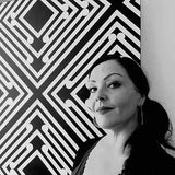 Black and white photo of NZ artist Anna Leyland and jewellery designer standing next to one of her paintings