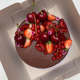 Double Chocolate cake with fresh cherries, redcurrants, strawberries and edible flowers