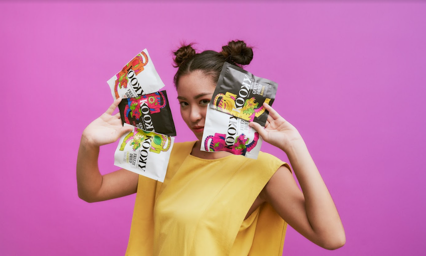 Woman with pouches of I Am Kooky gently dried and freeze-dried fruit