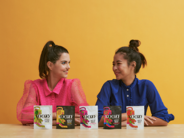 two women sat side-by-side with packets of Kooky freeze-dried fruit