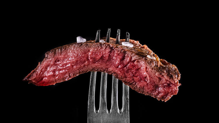 Beef meat rare on fork black background