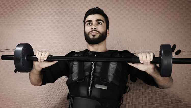 Closeup of handsome man lifting weights in EMS suit