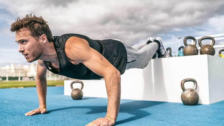 Decline push Up fitness man doing strength training exercise pushup at outdoor gym with elevated legs on jump box