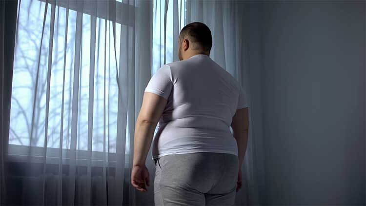 Fat man looking out through window, depressed introvert ashamed of obese body