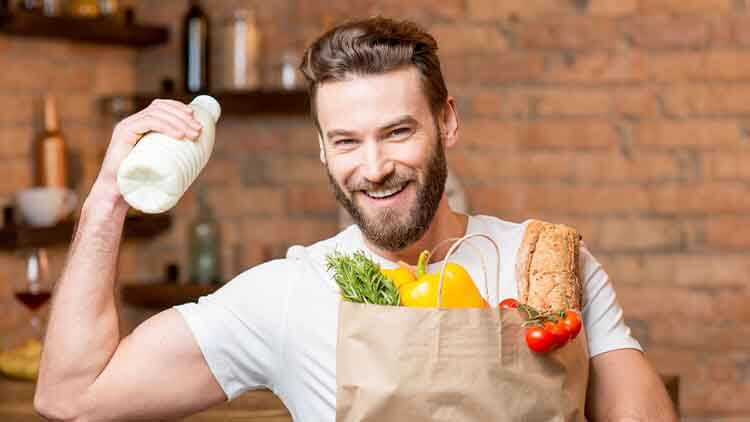 Handsome man holding milk with paper bag full of healthy food in the kitchen