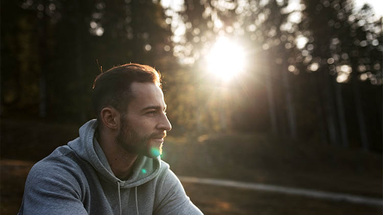 man wearing a grey hoodie sitting in a park and enjoying morning sun