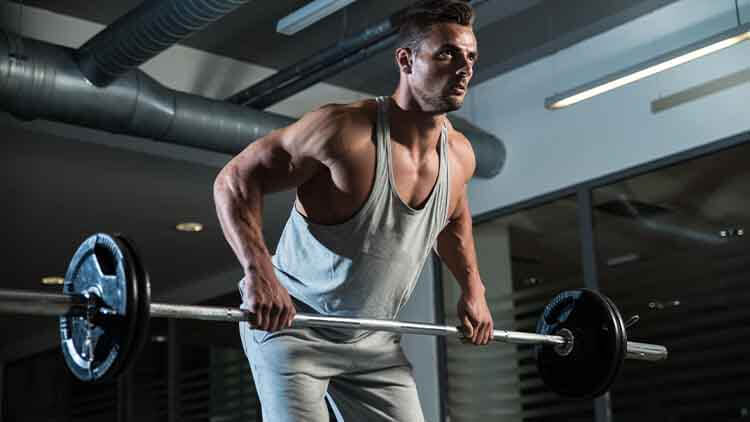 Pain and Gain - a man lifting barbells in a gym wearing grey coloured clothes