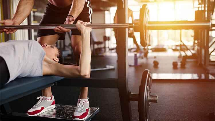 Personal trainer helping woman  with bench press