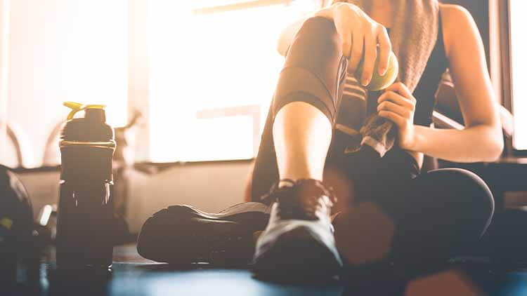 Sport woman sitting and resting after workout or exercise in fitness gym with protein shake or drinking water on floor.
