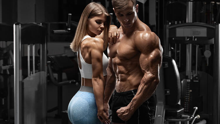 Sporty sexy couple showing muscle and workout in gym