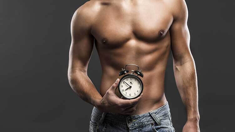 shirtless man holding a clock in his hands