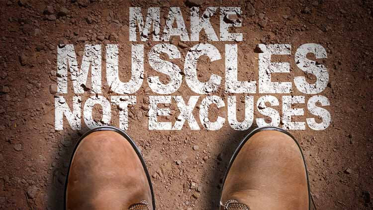 make muscles not excuses written in dirt with a top view of brown boots worn by a male