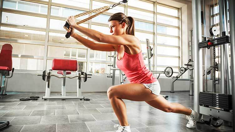 Young female with sport body doing workout at the gym.