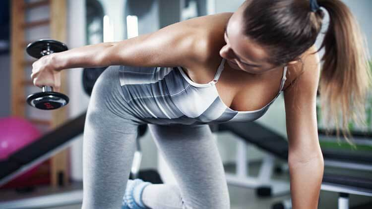 Young woman doing triceps exercise