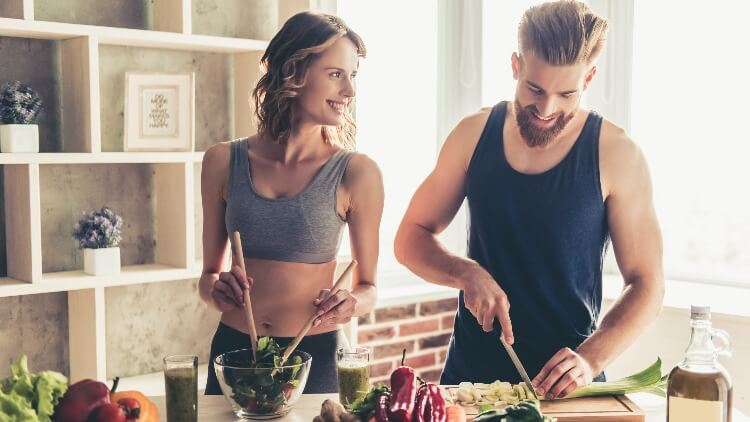 Athletic couple cooking healthy food together