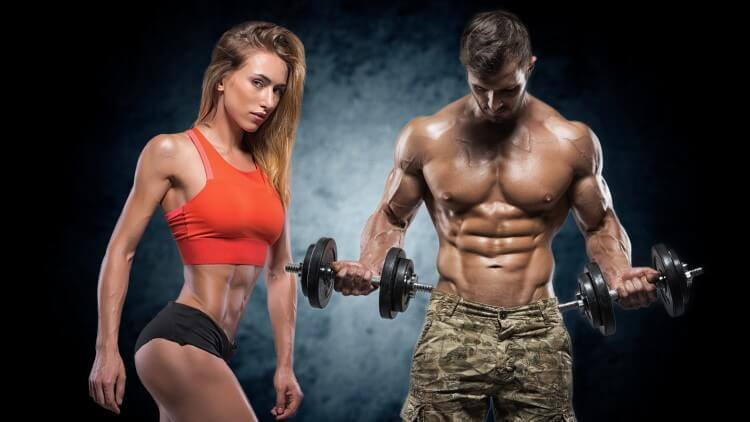 Man stood holding dumbbells next to athletic woman