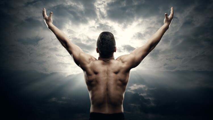 Athletic man with open arms pointing to sunrise in clouds
