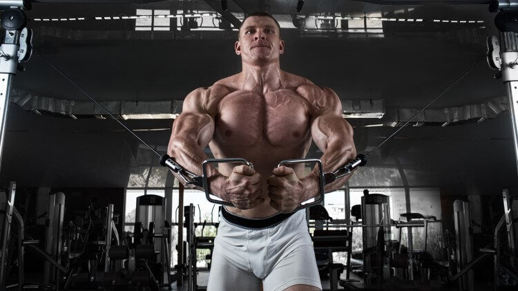 shirtless male bodybuilder doing crossover exercises in a gym