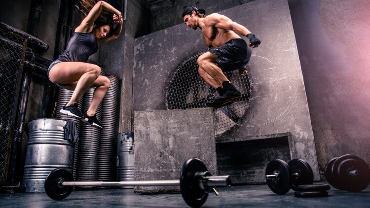 Couple training in gym jumping near weights