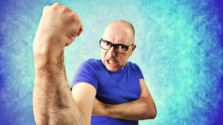 Crazy man showing bicep on bright blue background