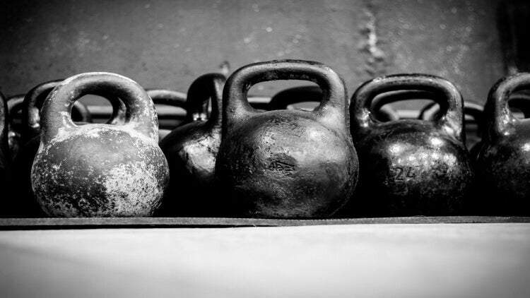 Old worn dumbells in gym in black and white