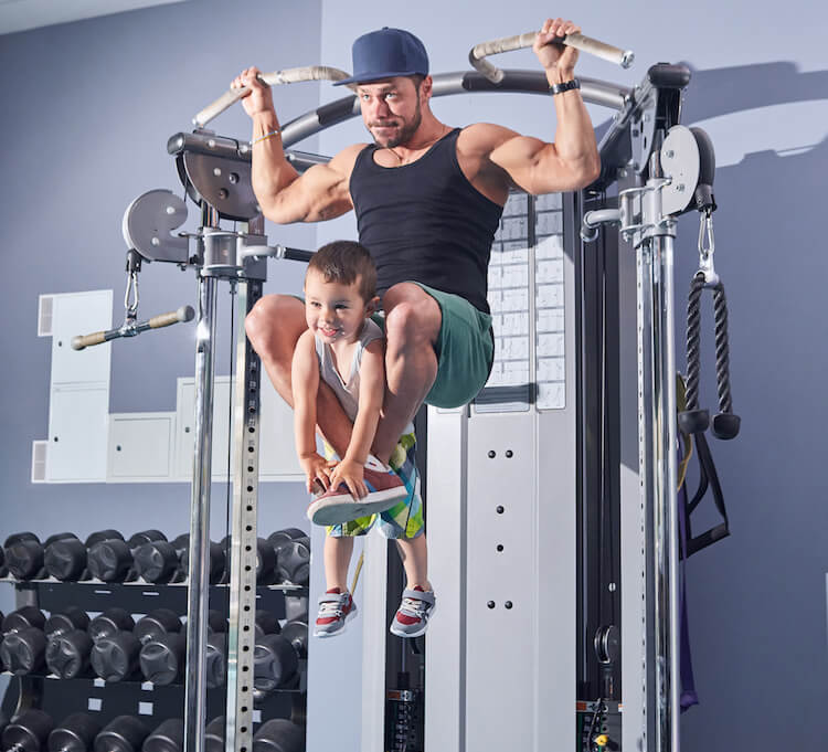 father excercising with his young son in a gym, holding him with his legs while he's working on his arms area