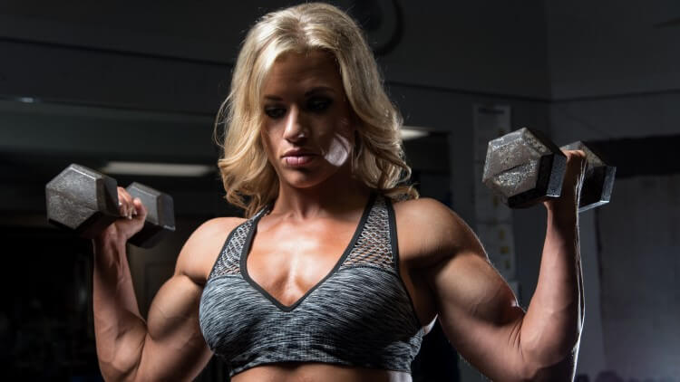 Female concentrating on dumbbell lifting