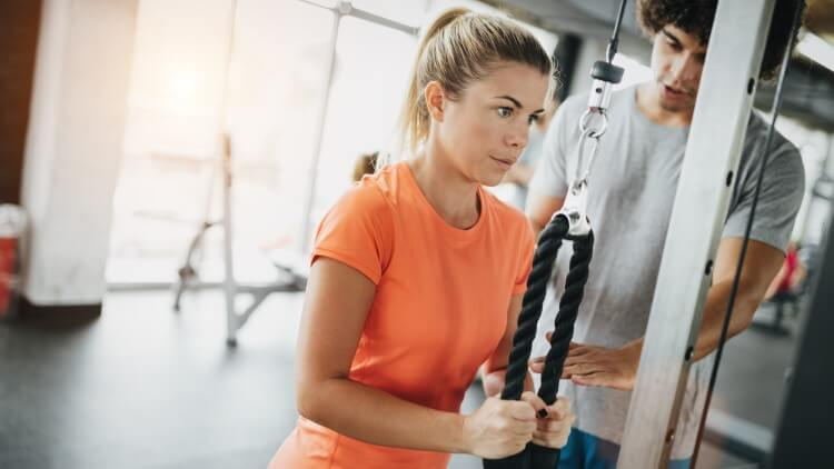 Girl working out with personal trainer in gym