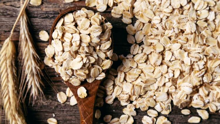 Oats on wooden spoon at on wooden table