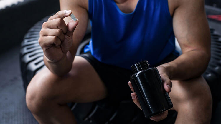 holding pills from bottle of pills at the gym