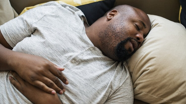 Man asleep on top of bed hands on chest