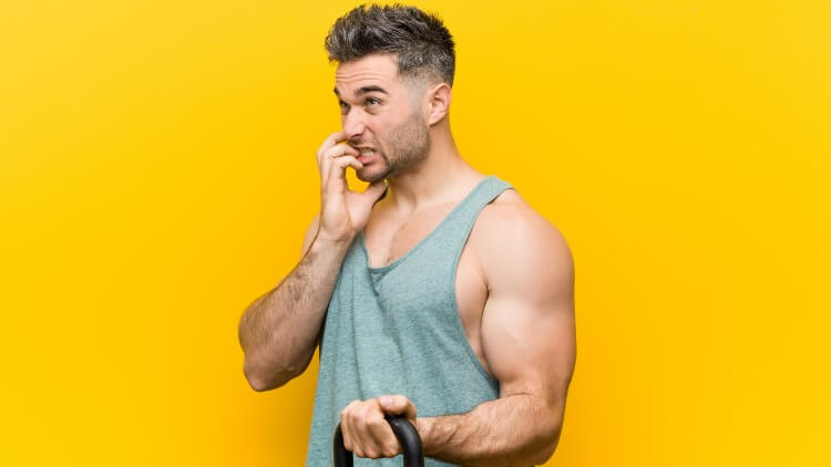 Man holding bumbell biting fingernails looking nervous yellow background