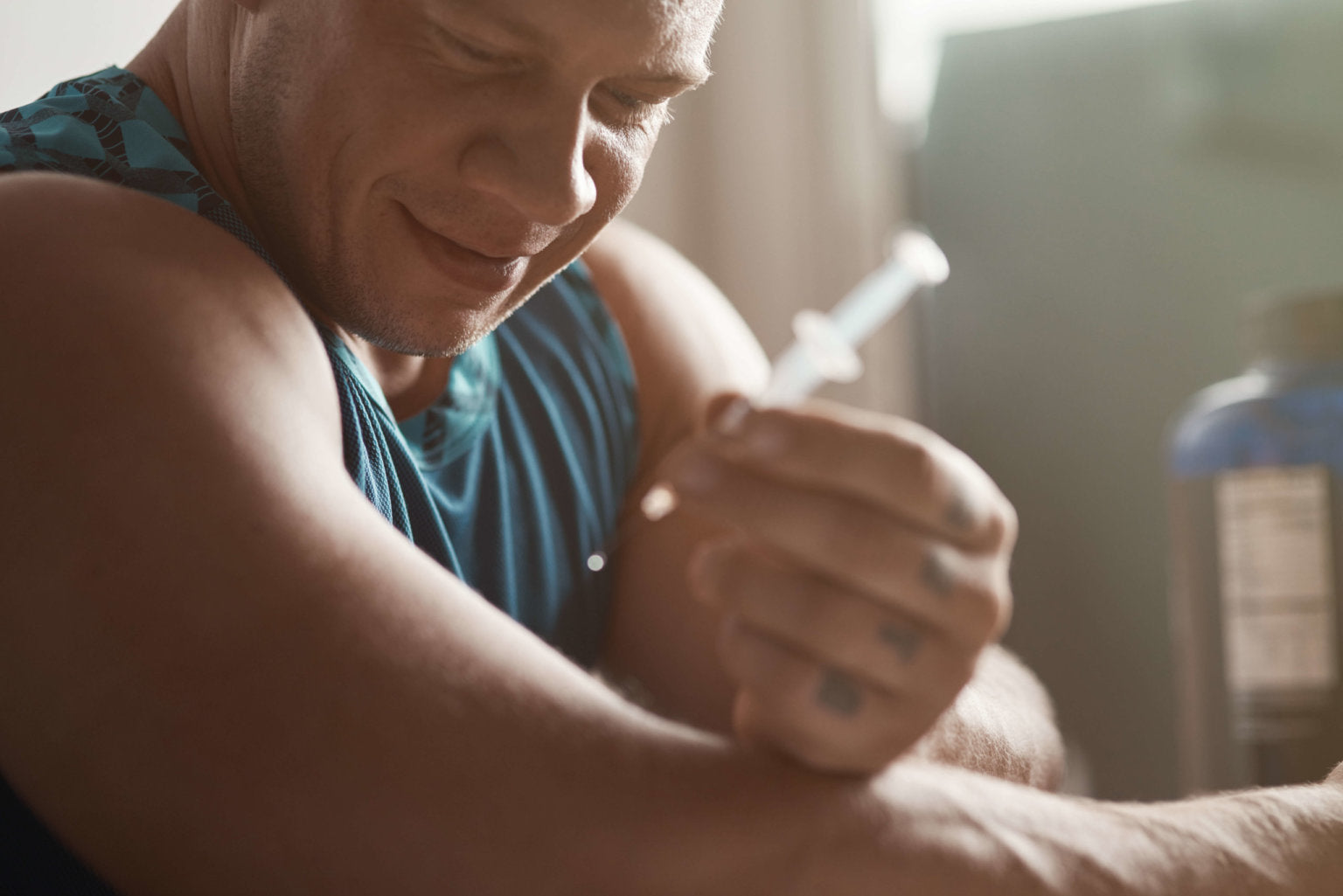Happy muscular man injecting into bicep