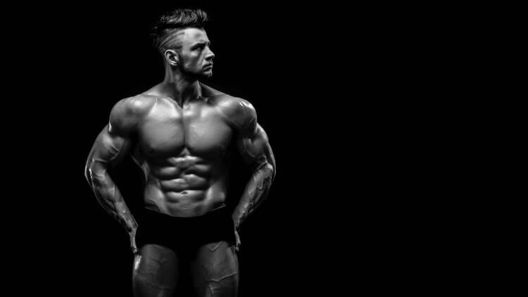 Muscular male model posing in front of black background
