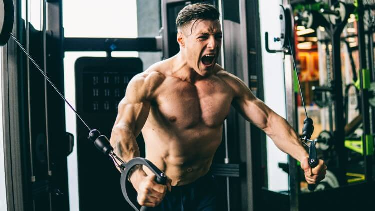 Muscular man in gym pumping chest with struggling expression