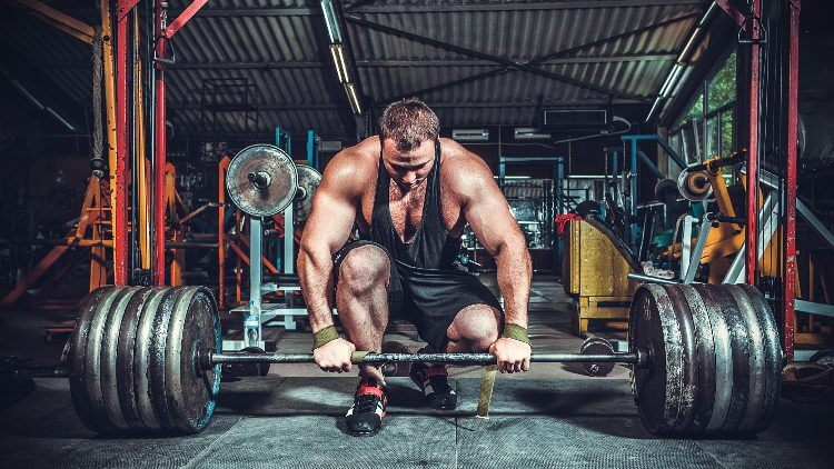 Muscular man power lifting in warehouse