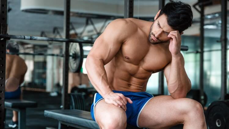Muscular man sat in gym on bench resting