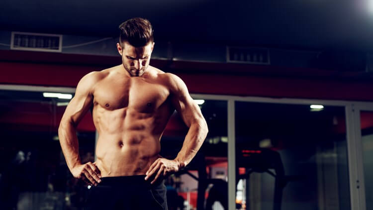 Muscular shirtless man holding hips looking down in gym