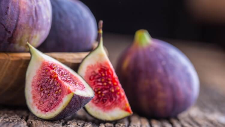 Sliced figs on wooden background
