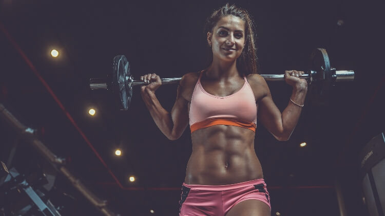 Young athletic woman holding weights above shoulders in gym