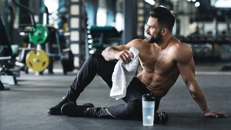 Young man resting on gym floor with towel and water