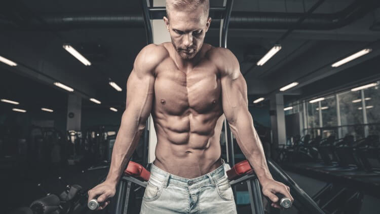 Young man with defined physique exercising in gym