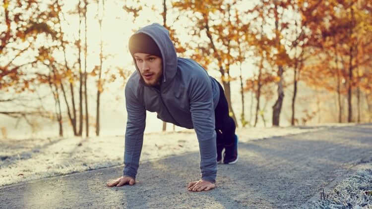 Young man doing push ups on cold autumn morning